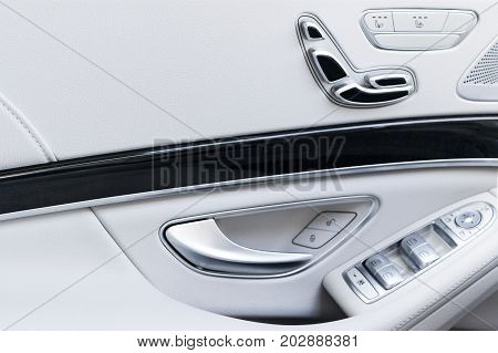 Door handle with Power seat contol buttons of a luxury passenger car. White leather interior of the luxury modern car. Modern car interior details