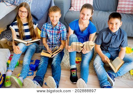 Row of teenager friends reading books at home