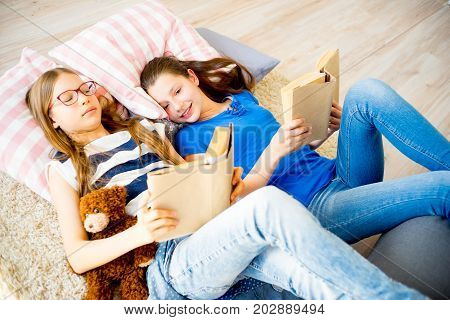 Two girls are reading books and lying