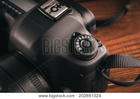 Camera On Vintage Wooden Boards Abstract Background. Professional Reflex Camera.