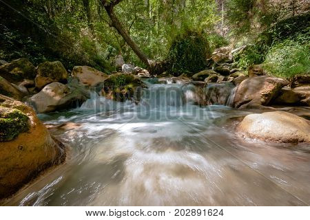 Photo from mountain river that runs usually in mountains in narrow deep valley with steep banks rocky stream bed and accumulated rock debris. Mountain rivers are characterized by high and flow velocity insignificant depth frequent rapids and waterfalls do