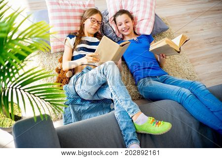Two sisters are reading books and lying