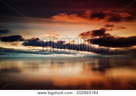 Evening colored sky with dark cumulus clouds over sea