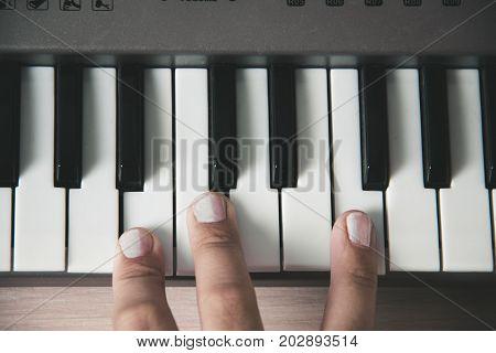 Beautiful girls fingers playing electronic piano keyboards