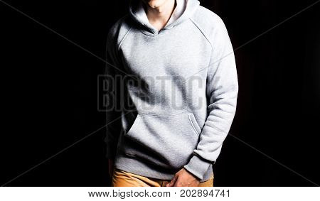 man in the blank grey hoodie sweatshirt on a black background mock up free space