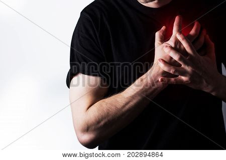 man guy in a black t shirt on a white background hold hands on his heart heart atack severe heartache chest myocardial infarction