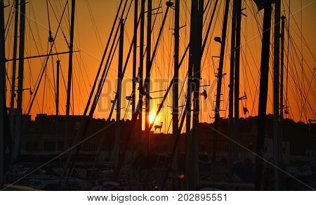 Sunset on Rhodes island Greece. View through masts of boats in marina