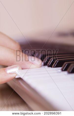 Beautiful girls hand playing electronic piano keyboards