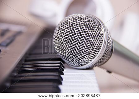 Close up on a microphone during recording session with a singer piano in the background music studio