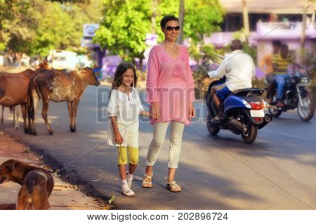 Mother and daughter walking on road with cows on background