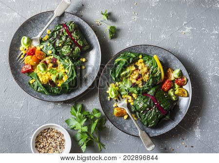 Swiss chard packets. Chard leaves stuffed with turmeric lentils and vegetables. Vegetarian healthy food concept. On a grey background top view