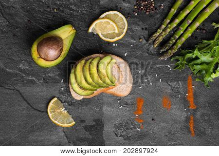 A stone table with green fresh asparagus, salad leaves, a sandwich with slices of sappy avocado on a gray background.