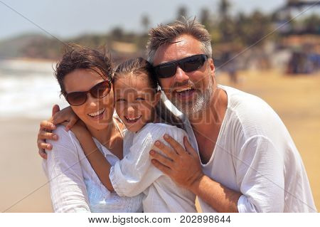 Portrait of happy family hugging on seashore