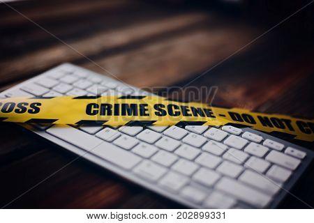 Yellow Crime Scene Tape On Computer Keyboard.