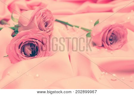 Close-up of rose flowers on pink satin fabric with bead strand. Vintage toning. Gentle romantic background