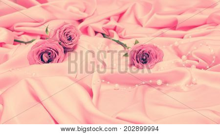Rose flowers on pink satin fabric with bead strand. Vintage toning. Gentle romantic background