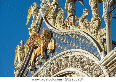 Angels and the lion on the top of the facade of Basilica di San Marco (Saint Mark`s Basilica) in Venice, Italy. The winged lion is a symbol of Venice.