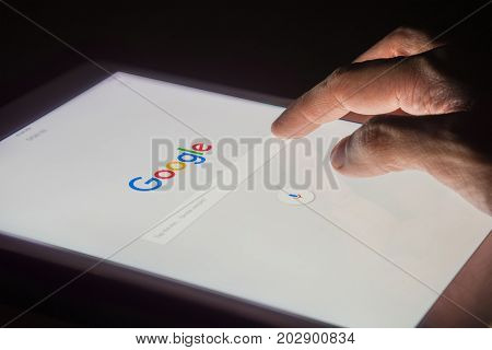 BANGKOK THAILAND - FEBRUARY 14 2017: A man's hand is touching screen on tablet at night for searching on Google search engine. Google is the most popular Internet search engine in the world.