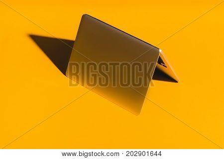 overturned stylish laptop standing on yellow background