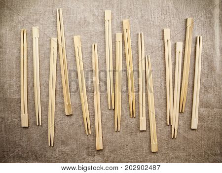 Many Asian wooden chopsticks arranged in a row background. Lots of Chinese traditional eating utensils