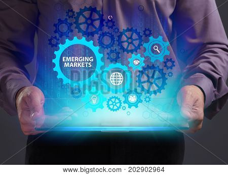 Business Technology Internet and network concept. Young businessman working on a virtual screen of the future and sees the inscription: Emerging markets
