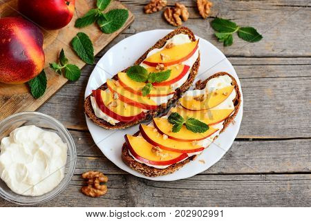 Vegetarian sandwiches with cream cheese, nectarines, walnuts and mint on a serving plate and on an old wooden background. Healthy lunch sandwiches idea. Closeup. Top view