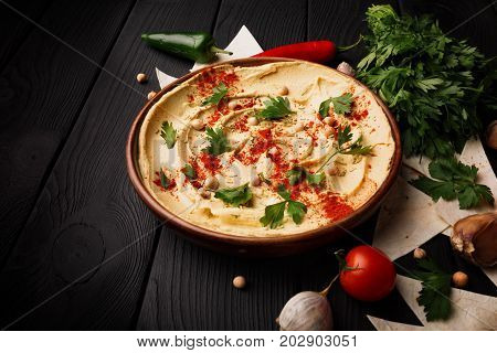 Close-up picture of a beautiful, nutritious, creamy hummus spread with natural ingredients on the black wooden table background. Appetizing hummus dip with thin pita bread slices and vegetables.