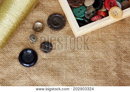 buttons and spool of thread on burlap background .