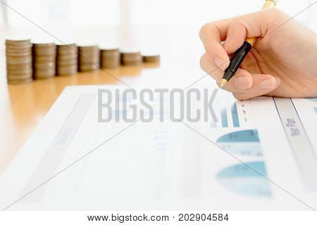 Business woman Analyzing Financial Graph With Coins