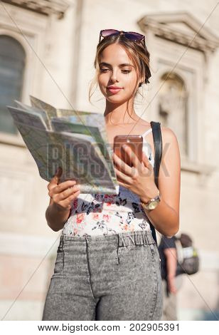 Gorgeous young brunette tourist woman using map and smart phone to navigate.