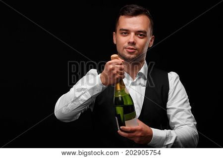 A charming bartender in a white shirt uncorks a bottle of champagne on a dark black background. Night club, party, cafe, restaurant, party, concept.