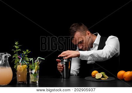 A handsome bartender wipes a metal shaker, a bar counter with limes, lemon, oranges and different cocktails on a black background. Cafe, restaurant, night club, party, concept.