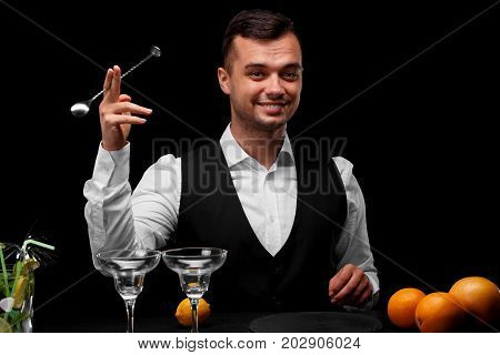 A bar counter with glasses for cocktails, lemon and oranges, a bartender with a spoon for shaker on a black background. Party, cafe, restaurant, night club, concept.