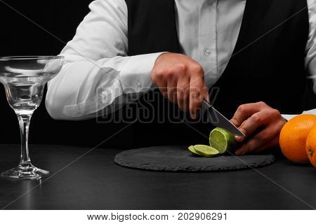 A bar counter with fresh vivid oranges, a glass for cockail, a bartender slices a sappy green lime with a knife on a black background. Night clubs, restaurant, cafe, party, concept.