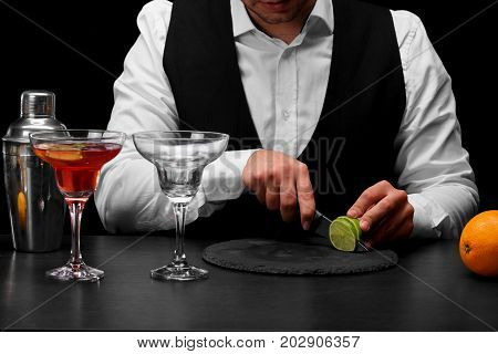 A bar counter with fresh succulent oranges, a margarita glass cockail, a bartender slices a sappy green lime with a knife on a black background. Night clubs, restaurant, cafe, party, concept.