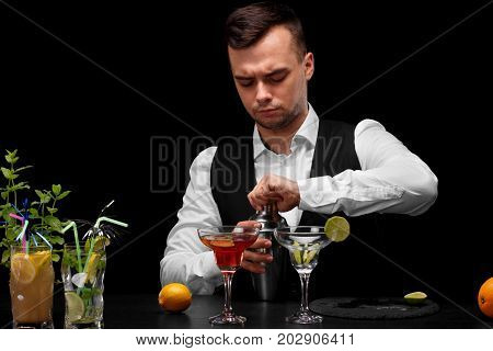 A bar counter with margarita glasses, slices of lime, lemon, a bartender who opens a shaker on a black background. Night club, cafe, restaurant, party, concept.