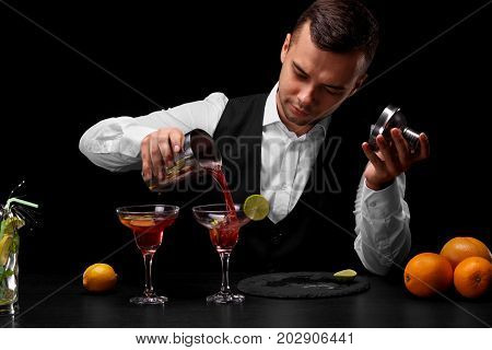 A bar counter with bright oranges, lemon and slices of lime, a charming bartender pours a cocktail in a margarita glass on a black background. Night club, cafe, restaurant, party, concept.