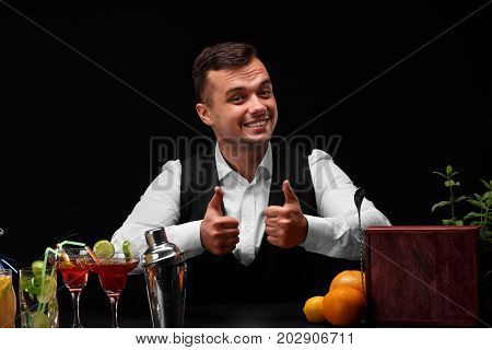 A bar counter with a metal shaker, margarita glasses, oranges, lemon, a bartender shows big thumbs up on a black background. Party, night club, cafe, restaurant concept.