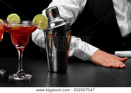 A bar counter with a shaker with drops of water, a margarita glass full of cocktail, a hand of a bartender on a black blurred background. Cafe, night club, party concept.