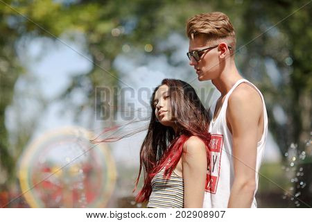 An appealing girl and an attractive fellow dating in a park on a natural blurred background. Dating, love, amusement, outdoor, parks concept.