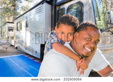 African American Father With Mixed Race Son In Front of Their Beautiful RV At The Campground.