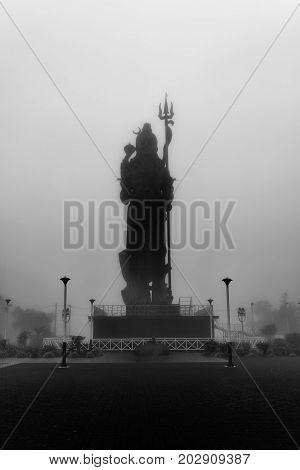 Black and white photoshot in a day with fog for create a mystical feel amazing statue of Lord Shiva (Mangal Mahadev) at Grand Bassin in Mauritius.