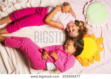 Children With Happy Faces Lie Close On Pink Blanket Background.