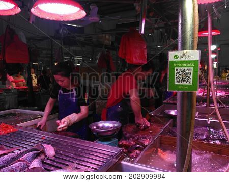 ZhongshanChina-September 3 2017:fish retailer in Chinese market with a Wechat QR code payment in front.QR code for payment and money transfering becomes very common and popular in China.