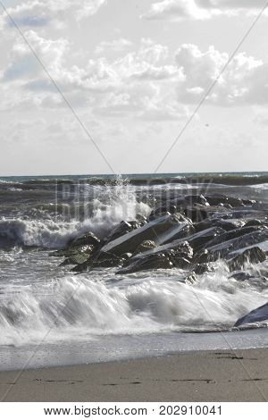 MARINA DI MASSA, ITALY - AUGUST 17 2015: Waves crashing into rocks in Marina di Massa Italy