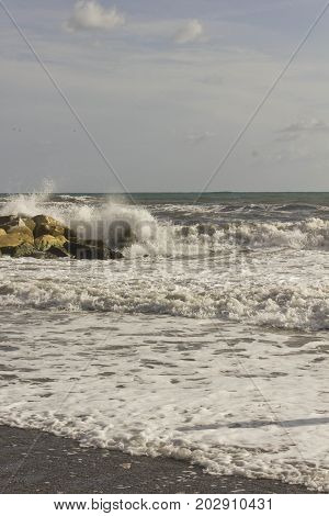 Wave smash into the rocks in a sunny day with rough seas in Tuscany