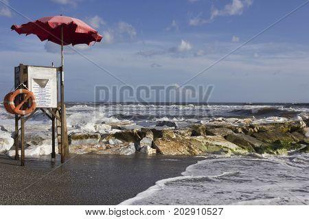MARINA DI MASSA, ITALY - AUGUST 17 2015: Lifeguard tower in Marina di Massa Italy near the cliff in a rough seas day