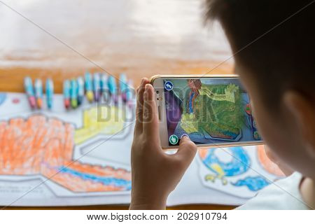 ZhongshanChina-August 19 2017:kid playing Augmented Reality popup paintings of a color filled Great Wall via mobile. AR and VR games become more and more popular.