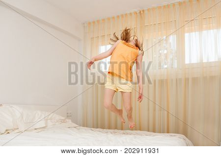 The girl is jumping in the bedroom. Happy child girl having fun jumps and plays bed.