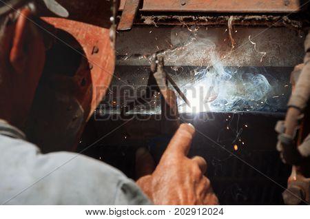 Welder erecting technical steel. Industrial steel welder. Craftsman in factory. The welder is engaged in repair of equipment in an industrial plant. Sparks of welding.